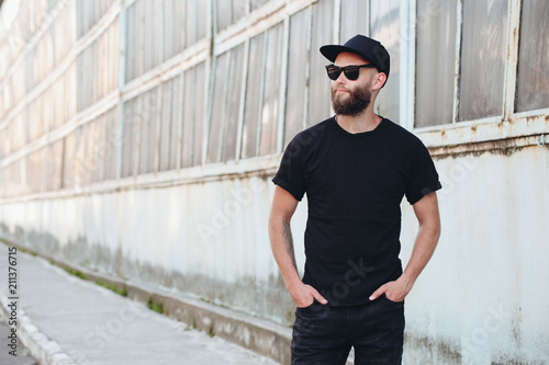 Obraz Hipster handsome male model with beard wearing black blank t-shirt with space for your logo or design in casual urban style - fototapety do salonu