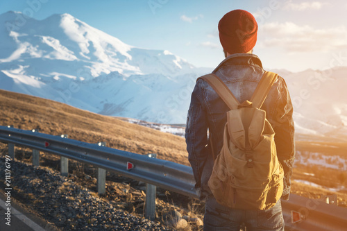 Obraz Bearded tourist hipster man in sunglasses with a backpack stand back on a roadside bump and watching the sunset against the background of a snow capped mountain - fototapety do salonu