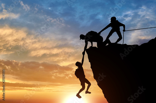 Photo Stands Mountaineering Silhouette of three male climbers rescuing another male climber pulling his arm