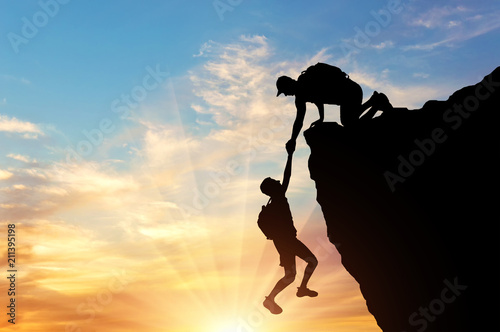 Silhouette of a climber saves another climber pulling him from the abyss