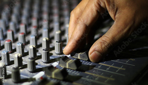 hands operating knobs of light and sound board console at a concert