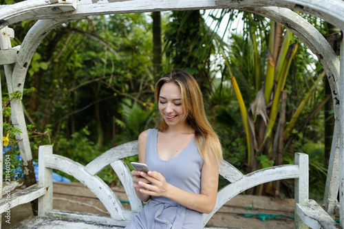 Fotografía  Young woman riding on swing and using smartphone in exotic garden, palms in background