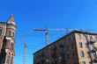 high tower cranes over ancient houses