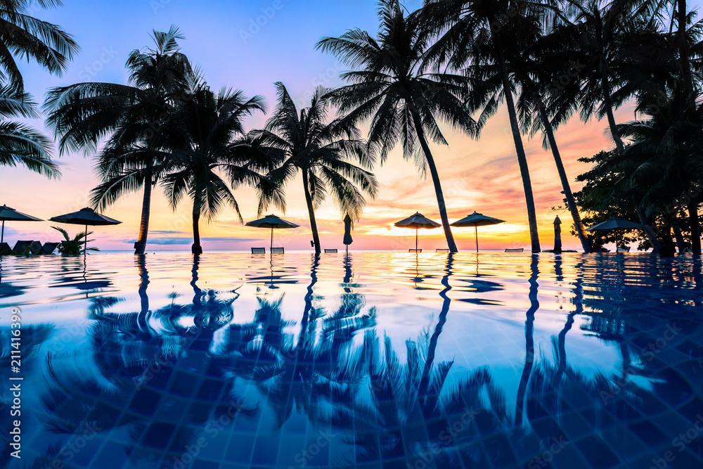 Fototapeta Summer beach holiday vacation destination, luxurious beachfront resort swimming pool with tropical landscape, quiet warm sunset, silhouette and reflection in water