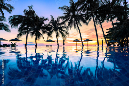 Spoed Foto op Canvas Grijze traf. Summer beach holiday vacation destination, luxurious beachfront resort swimming pool with tropical landscape, quiet warm sunset, silhouette and reflection in water