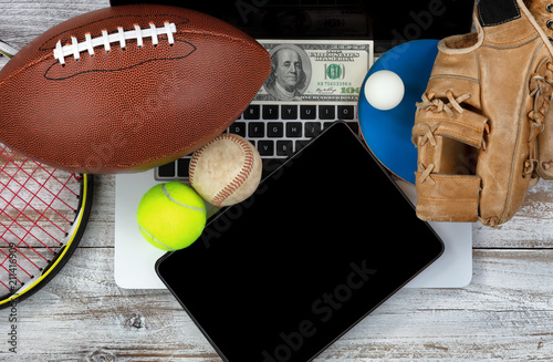 Fotografía  Betting on various sports with computer technology and money in background