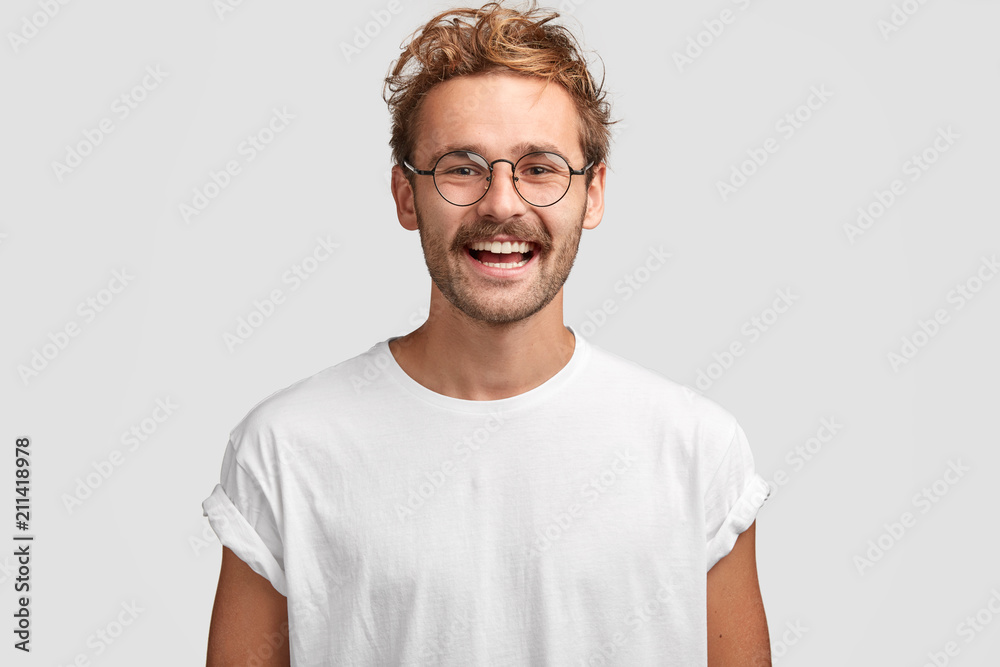 Fototapeta Horizontal shot of happy hipster male with toothy smile, wears casual white t shirt and glasses, being in good mood after unforgettable journey with girlfriend, isolated on white background.