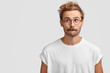 canvas print picture - Puzzled handsome male with mustache, bites lower lip and looks curiously aside, thinks about something, dressed in casual white t shirt, stands against blank wall with copy space for your text