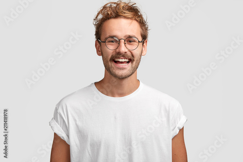 Horizontal shot of happy hipster male with toothy smile, wears casual white t shirt and glasses, being in good mood after unforgettable journey with girlfriend, isolated on white background Fototapeta