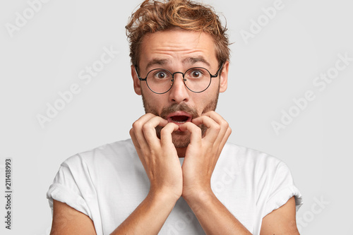 Headshot of attractive male looks with surprised scared nervous expression, has problem on work, bites fingernails, dressed casually, recieves bad news from colleagues. People, reaction concept