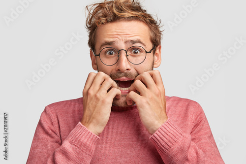 Emotive depressed young embarrassed man bites fingernails in panic, looks with nervous expression, going to cry with worried look, recieves negative awful news, poses against white background.