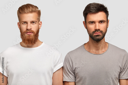 Valokuva  Bearded serious male friends with trendy haircut, stand close to each other, think where spend free time, dressed casually