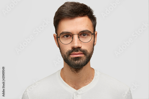Close up portrait of handsome unshaven male with thick beard and mustache, has dark hair, looks seriously at camera, thinks about something, isolated over white background Fototapet