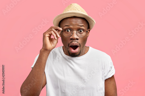 Fotografía Emotive stunned young African American male opens mouth and stares through glasses, being shocked by latest news, wears fashionable straw hat, stands alone against pink background