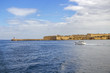 A motorboat passes along the Ricasoli Fort and Ricasoli Breakwater Lighthouse