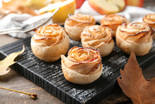 Wooden Board With Apple Roses From Puff Pastry On Table, Closeup