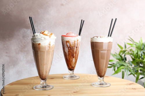 Photo Stands Milkshake Glasses with delicious milk shakes on table