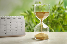 Hourglass And Calendar On Tabl...