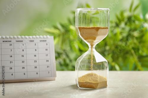 Slika na platnu Hourglass and calendar on table against blurred background