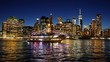 Ship navigating Hudson River against Cityscape of Lower Manhattan New York City at night