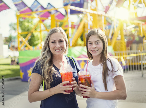 Two happy girls drinking a sweet beverage at an amusement park or summer carnival. Enjoying a cool drink on a warm summer evening