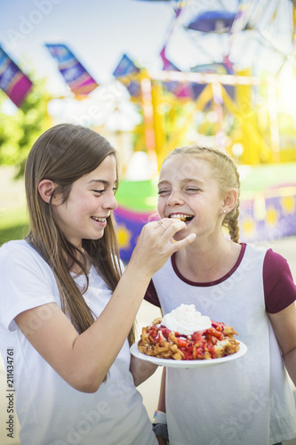Keuken foto achterwand Amusementspark Two laughing and smiling teenage girls eating a funnel cake at an outdoor carnival or amusement park. Cute expression in this candid photo