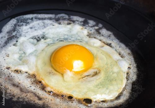 Foto op Plexiglas Gebakken Eieren An fried egg in butter in a carbon steel frying pan