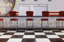 Vintage Diner Counter With Red Stools And Checked Floor, 3d Render.