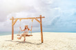 Woman sit at swing chair on the beach, cloud sky and nice beach sand background.