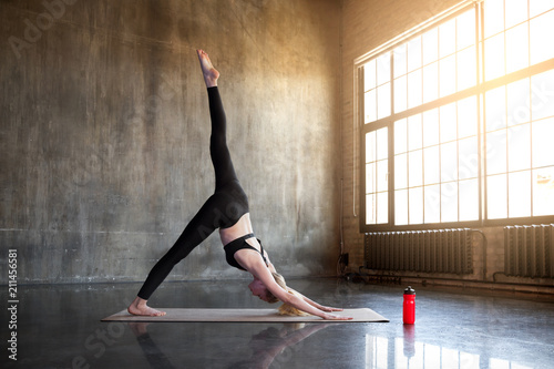 Tuinposter School de yoga Flexible modern woman doing yoga practice in a loft studio, surrounded by bright sunlight.
