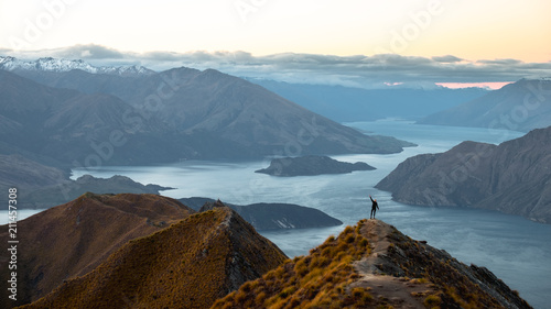 Tuinposter Blauw A woman looking at the beautiful landscape of the mountains and Lake Wanaka. Roys Peak Track, South Island, New Zealand.