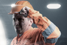 Portrait Of Tired Rail Worker With Orange Unifom And Helmet Light In Front Of Tunnel