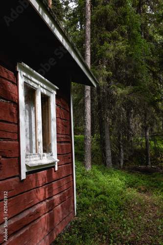 Old red timber cottage in the forest.