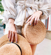 Stylish Woman's Outfit. Nature Stylish Top. Straw Bag. White Dress.Woman Hands With Fashionable Stylish Nude Rattan Bag And Straw Bag Outside. Stylish Young Woman Fashion Details.