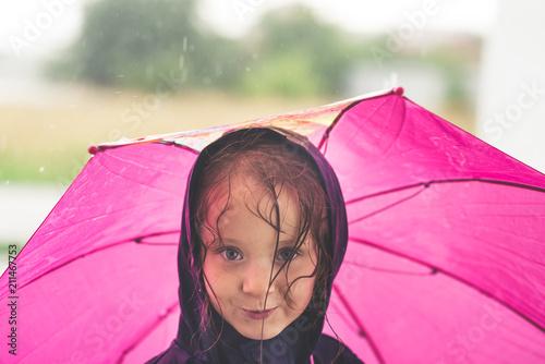 Fotografia  Little girl playing alone outside in bad weather. Summer rain