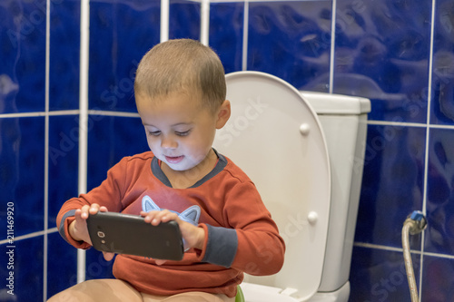 Cute toddler boy with smartphone in the bathroom Canvas Print