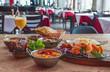 canvas print picture - Indisches Essen mit Nan, Masal, Salat, Chicken Tandoori,  Tikka, Spinat, Basmati schön angerichtet in einem Restaurant auf einem Holztisch serviert