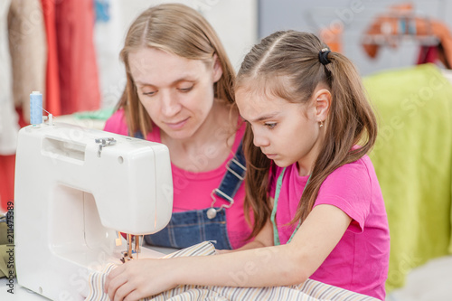 Fototapeta mother and little girl together sews on sewing machine