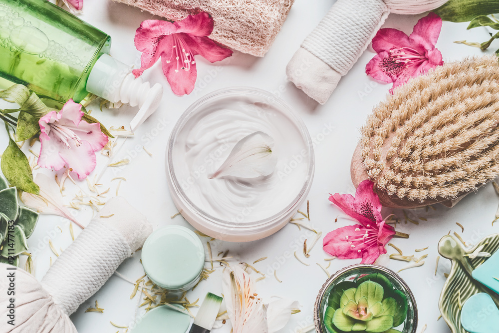 Fototapeta Skin cream with flowers petals and others body care cosmetic products and accessories on white background, top view