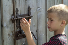 Young Blond Cute Boy Trying To Open Rusty Slide Bolt Lock On Lit By Sun Closed Old Wooden Barn Door. Children Curiosity, Love For Adventures, Safety, Security And Protection From Thieves Concept.