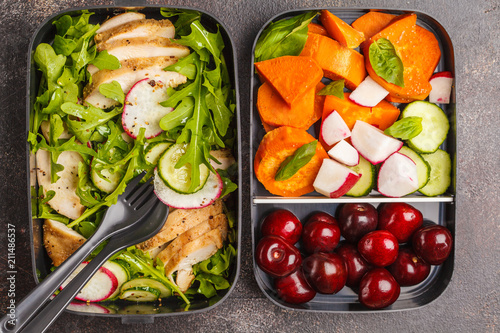 Healthy meal prep containers with grilled chicken with salad, sweet potato, berries, fruits and vegetables. Dark background, top view.