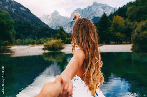 Attractive young woman holding hand of her friend and walking next to the lake