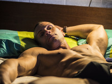 Nude Muscular Man With Perfect Body Posing On Bed In Soft Light At Night
