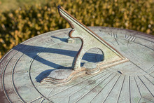 A Vintage Sundial With Green Patina Throws A Long Shadow, Tracking The Motion Of The Sun While Telling The Time Of Day.