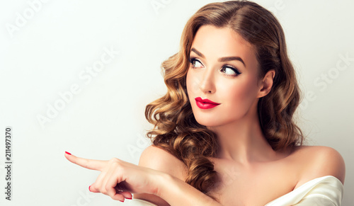 Obraz Woman surprise showing product .Beautiful girl  with curly hair  pointing to the side . Presenting your product. Isolated on white background. Expressive facial expressions