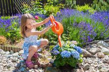Little Girl Watering Flowers In A Garden