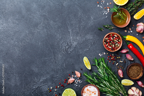 Tuinposter Kruiderij Different spices and herbs on black stone table top view. Ingredients for cooking. Food background.