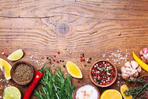 Spoed Foto op Canvas Kruiderij Set of spices and fresh rosemary on wooden kitchen table top view. Ingredients for cooking. Food background.