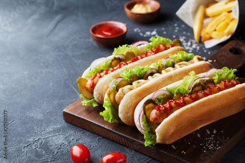 Hot dog with grilled sausage, ketchup, mustard and fries closeup Fototapeta