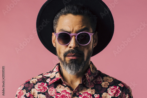 Fotografía  Portrait of a trendy man with silver beard, sunglasses and hat, isolated on pink